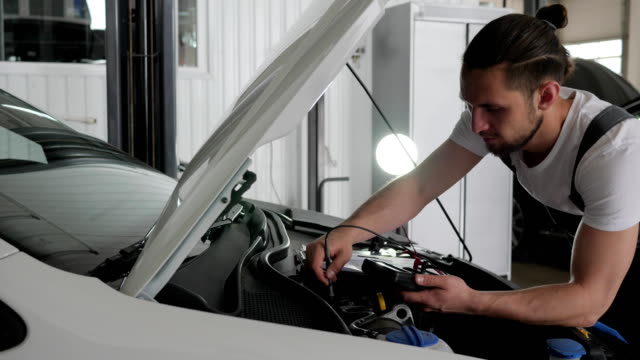 Estación-de-servicio-soportes-macho-mechanician-profesionales-cerca-de-campana-abierta-comprueba-cableado-sistema-automóvil-revisión-de-motor-estado-técnico