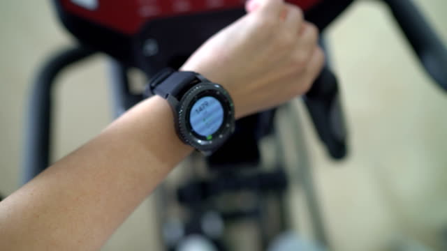 PoV-of-woman-doing-cardio-on-elliptical-trainer-checking-workout-on-smart-watch