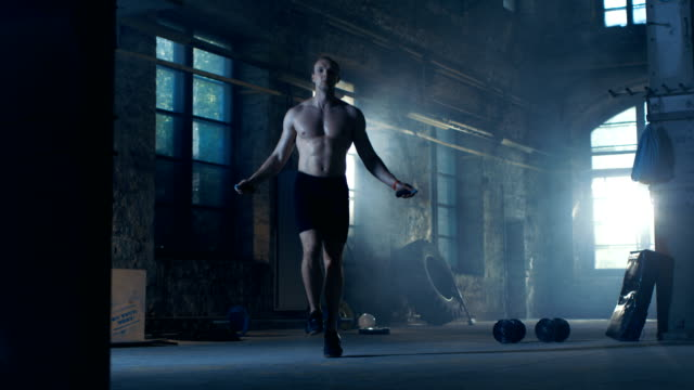 Athletic-Shirtless-Fit-Man-Exercises-with-Jump-/-Skipping-Rope-in-a-Deserted-Factory-Hardcore-Gym-He-s-Covered-in-Sweat-from-His-Intense-Fitness-Training-