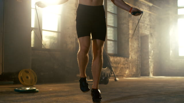 Hombre-ajuste-camisa-atlética-ejercicios-con-salto-/-saltar-cuerda-en-un-gimnasio-de-Hardcore-de-fábrica-abandonada-Está-cubierta-en-el-sudor-de-su-intenso-entrenamiento-