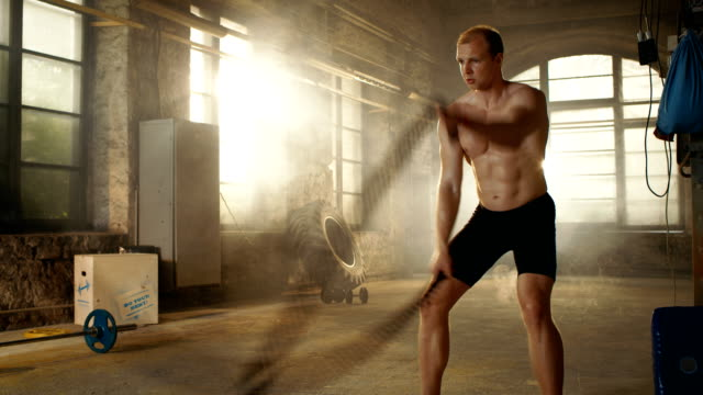 Muscular-Shirtless-Man-in-a-Gym-Exercises-with-Battle-Ropes-During-Her-Fitness-Workout/-High-Intensity-Interval-Training-
