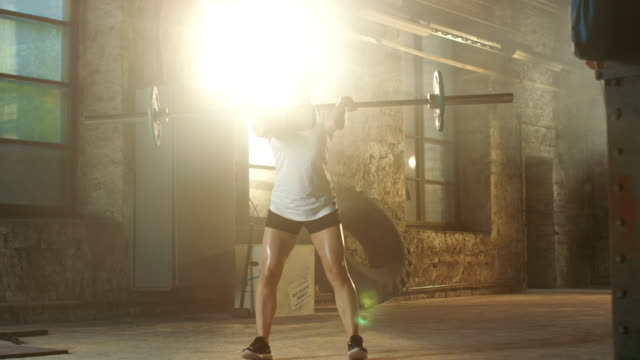 Strong-Athletic-Woman-in-Sportswear-Lifts-Heavy-Barbell-and-Does-Squats-with-it-as-a-Part-of-Her-Fitness-Training-Routine-Gym-is-in-Remodeled-Factory-
