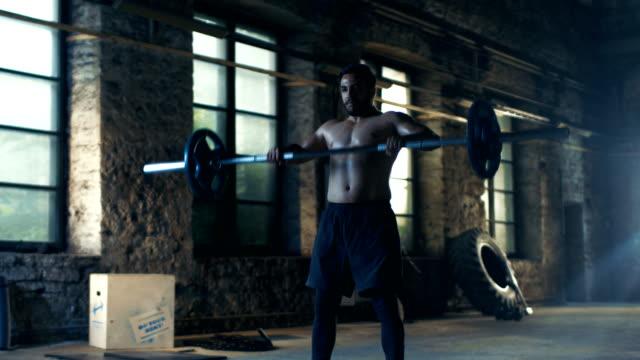 Hombre-musculoso-trenes-con-barra-en-gimnasio-Industrial-Hace-peso-muerto-Press-militar-y-agarre-inverso-rizos-