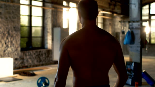 Follow-up-Shot-of-Muscular-Shirtless-Man-Entering-Gym-in-Slow-Motion-He-s-Confident-Building-is-Industrial-and-Hardcore-Various-Cross-fitness/-Bodybuilding-Equipment-lying-on-the-Floor-