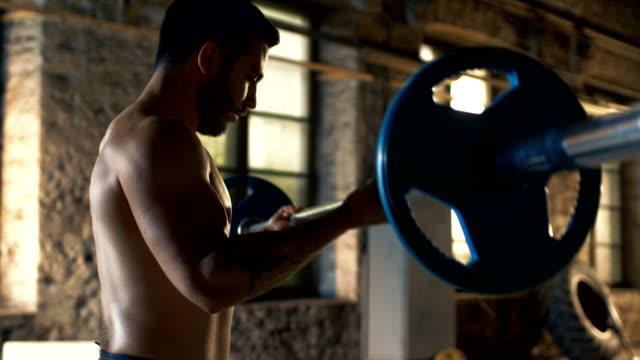 Camisa-hombre-elevación-pesada-barra-con-esfuerzo-haciendo-bíceps-rizos-/-culturismo-ejercicio-en-el-edificio-de-gimnasio-Industrial-