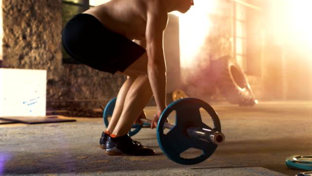 Hombre-sin-camisa-de-entrenamiento-levantar-la-barra-en-gimnasio-Industrial-Hace-peso-muerto-Press-militar-y-agarre-inverso-rizos-