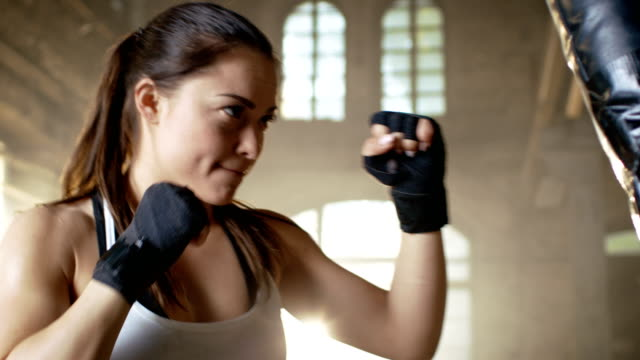 Woman-Fighter-Training-with-Punching-Bag-that-Her-Partner-Holds-She-s-Athletic-and-Has-Powerful-Punch-