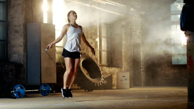 Hermosa-mujer-atlética-ejercicios-con-salto-/-saltar-cuerda-en-un-gimnasio-Ella-hace-parte-de-su-entrenamiento-físico-intenso-
