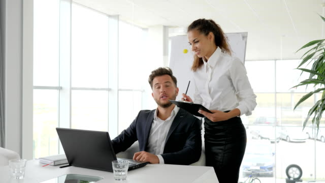 business-people-on-background-flipchart-in-white-office-boss-at-table-director-and-employee-assistant-keep-in-hands