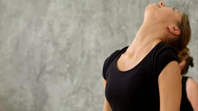 El-grupo-de-mujeres-jóvenes-tiene-clase-de-yoga-haciendo-poses-de-Guerrero-en-el-gimnasio