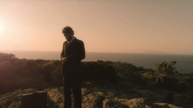 Man-in-elegant-suit-straightens-his-jacket-on-top-of-a-cliff-on-an-island