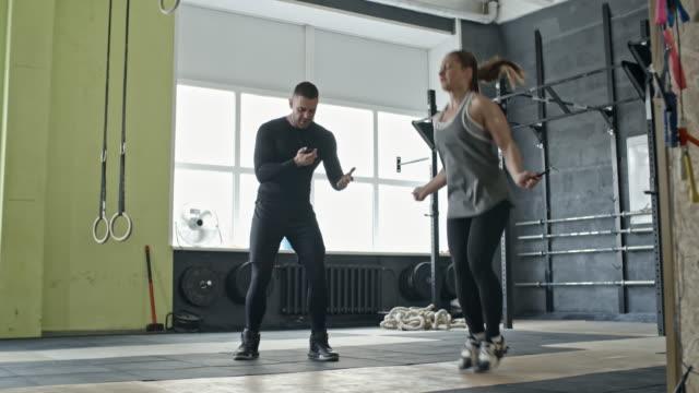 Entrenador-personal-motivación-mujer-durante-ejercicio-de-saltar-la-cuerda