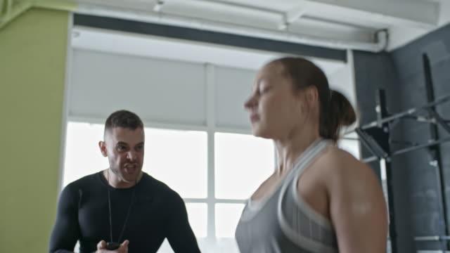 Muscular-mujer-saltando-la-cuerda-con-Entrenador-Personal