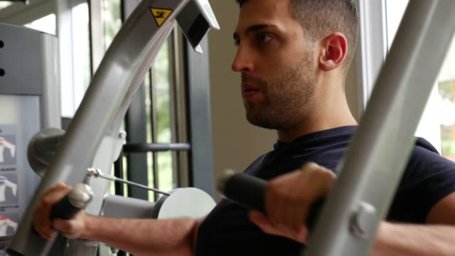Young-man-doing-chest-exercise-at-gym