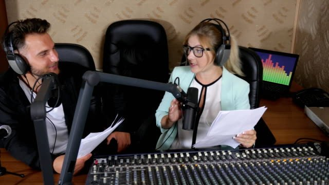 nice-radio-presenters-male-and-girl-in-headphones-talks-into-microphone-near-audio-console-indoors