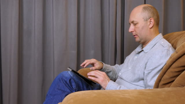 Man-sits-on-armchair-with-tablet-and-speaks-with-somebody-
