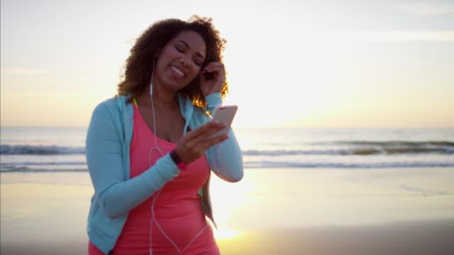 Ethnic-female-taking-beach-selfie-in-sun-flare