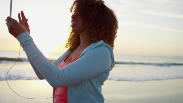 Ethnic-female-walking-at-sunset-in-sun-flare
