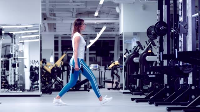 Posición-en-cuclillas-de-mujer-fitness-para-fortalecer-piernas-y-glúteos-calentamiento-se-pone-en-cuclillas-con-pesas-Atleta-hace-calentamiento-sentadillas-con-pesas