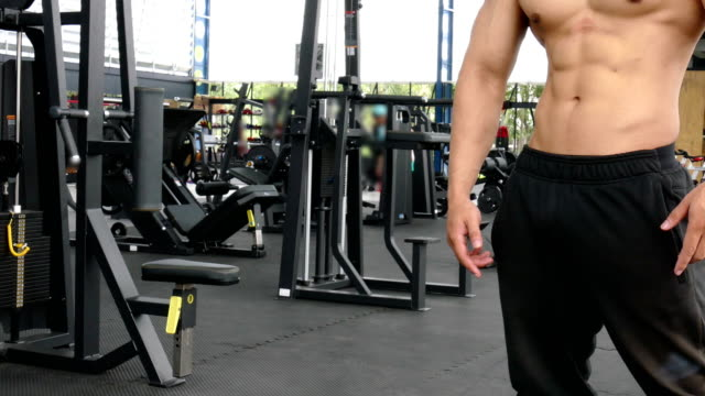 young-man-athlete-prepare-for-training-in-gym-bodybuilder-male-working-out-in-fitness-center-sport-guy-doing-exercises-in-health-club-sport-healthy-lifestyle-concept
