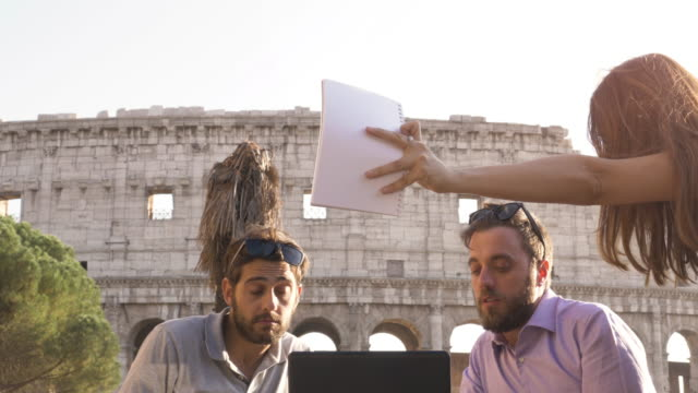Three-young-people-having-job-videocall-with-laptop-working-outside-together-pitching-a-project-sitting-at-bar-restaurant-table-in-front-of-colosseum-in-rome-at-sunset