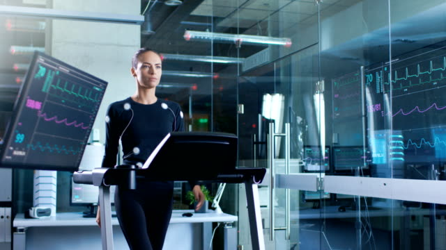 Beautiful-Woman-Athlete-with-Electrodes-Connected-to-Her-Body-Walks-on-a-Treadmill-in-a-Sports-Science-Laboratory-In-the-Background-High-Tech-Laboratory-with-Monitors-Showing-EKG-Readings-
