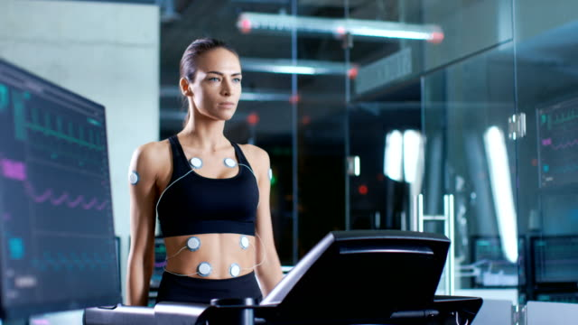 Beautiful-Woman-Athlete-Wearing-Sports-Bra-with-Electrodes-Connected-to-Her-Walks-on-a-Treadmill-in-a-Sports-Science-Laboratory-In-the-Background-Laboratory-with-Monitors-Showing-EKG-
