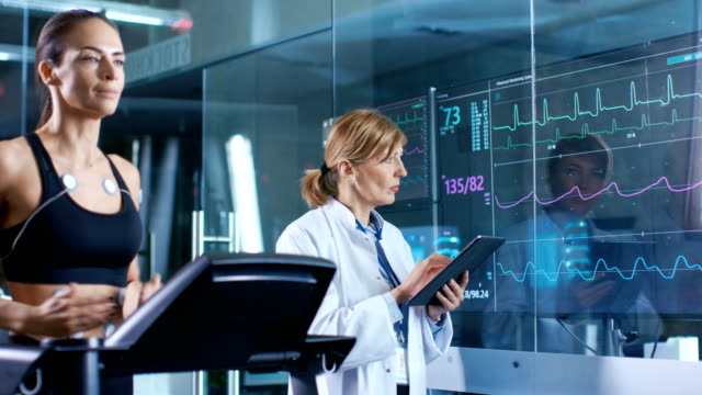 Beautiful-Woman-Athlete-Runs-on-a-Treadmill-with-Electrodes-Attached-to-Her-Body-Female-Physician-Uses-Tablet-Computer-and-Controls-EKG-Data-Showing-on-Laboratory-Monitors-