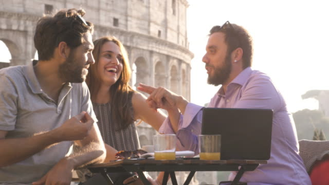 Three-young-friends-having-fun-laughing-with-laptop-and-tablet-sitting-at-bar-restaurant-table-in-front-of-colosseum-in-rome-at-sunset