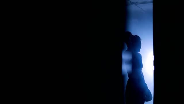 Detailansicht-einer-jungen-Frau-mit-einer-Pause-nach-einem-harten-Training-auf-einen-Boxsack-Silhouetten-von-eine-Boxerin-trainiert-in-einen-dunklen-Fitnessraum-mit-Boxsack