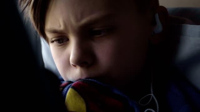 Kid-using-tablet-on-window-sill