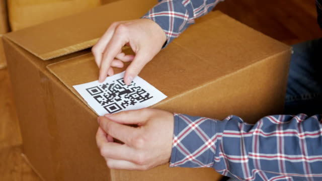 Un-hombre-pega-un-código-QR-en-una-caja-Servicio-de-entrega-Tienda-en-línea-Código-de-barras-