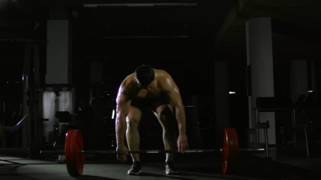 Muscular-culturista-haciendo-peso-muerto-con-barra