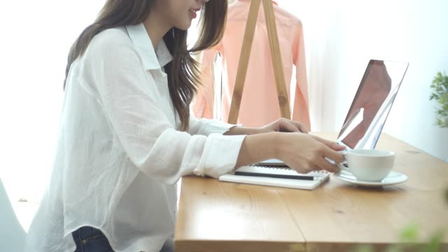 Beautiful-young-smiling-woman-working-on-laptop-while-enjoying-drinking-warm-coffee-sitting-in-a-living-room-at-home-Enjoying-time-at-home-Asian-business-woman-working-in-her-home-office-