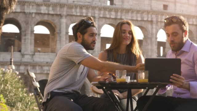 Three-young-people-with-laptop-and-tablet-talking-and-discussing-sitting-at-bar-restaurant-table-in-front-of-colosseum-in-rome-at-sunset