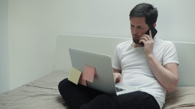 Busy-man-is-talking-by-cell-phone-and-typing-on-laptop-sitting-in-his-bedroom