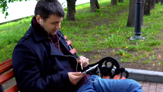 A-man-listens-to-music-and-works-on-a-tablet-in-the-park-
