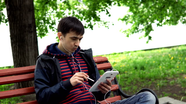 The-man-is-using-a-tablet-in-the-park-