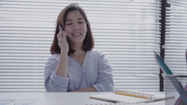 Beautiful-young-smiling-asian-woman-working-on-laptop-while-sitting-in-a-living-room-at-home-Asian-business-woman-using-phone-for-work-in-her-home-office-Enjoying-time-at-home-