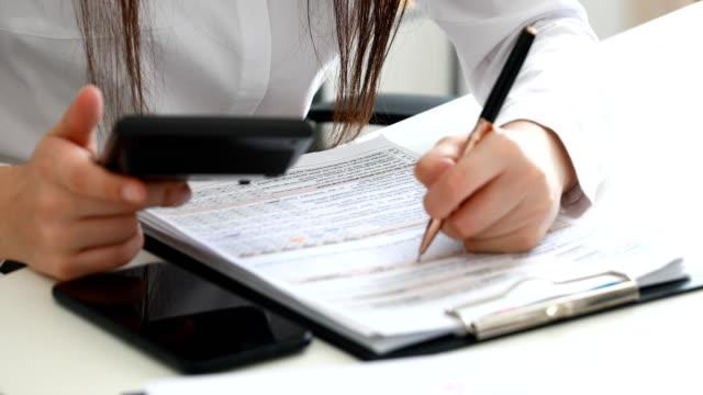 manos-de-mujer-con-calculadora-y-llenado-de-documentos-en-la-oficina-moderna