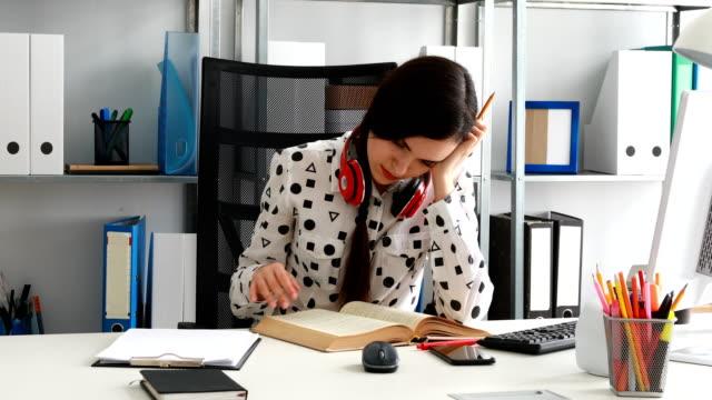 mujer-con-auriculares-rojo-con-hombros-hojeando-el-libro-en-la-oficina-moderna