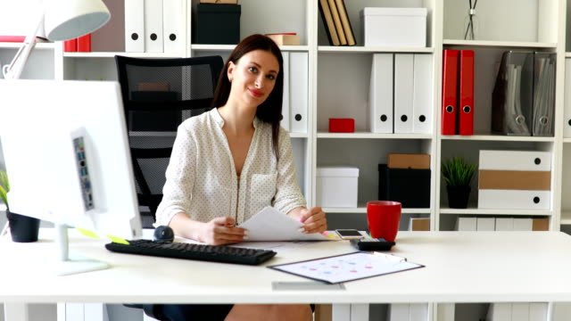 businesswoman-in-white-blouse-sitting-at-table-and-looking-at-camera