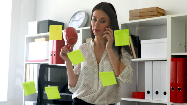 businesswoman-in-white-blouse-considering-stickers-on-glass-and-talking-on-phone