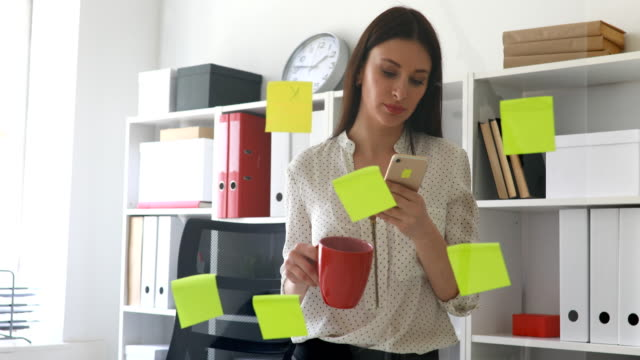businesswoman-standing-near-glass-wall-with-sticky-notes-and-using-smartphone