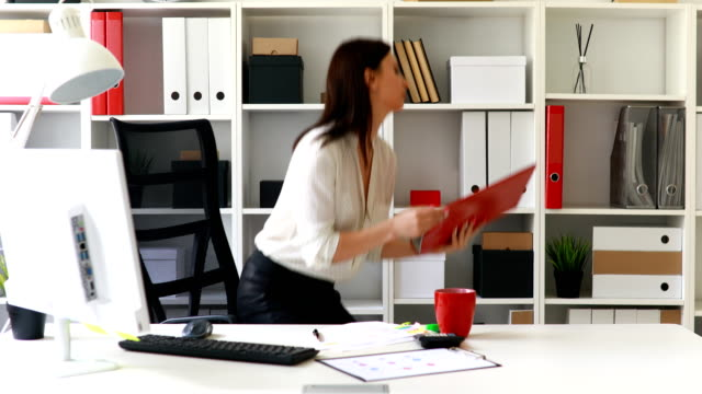 businesswoman-in-black-skirt-putting-folder-in-cabinet