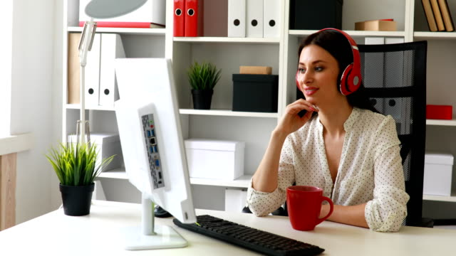 businesswoman-listening-music-looking-to-monitor-and-waving-hand-at-camera
