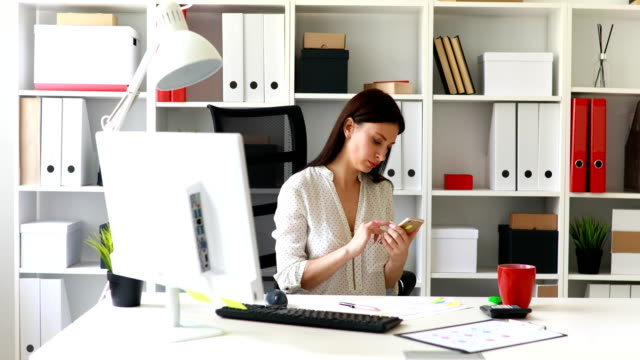 businesswoman-sitting-in-office-chair-and-using-smartphone