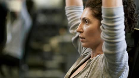 Motivated-Woman-Exercising-with-Dumbbells-in-Gym