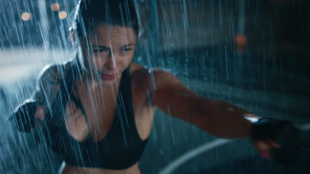 Beautiful-Sporty-Fitness-Girl-is-Doing-Sharowboxing-Exercises-She-is-Doing-a-Workout-at-Night-in-Heavy-Rain-with-One-Light-Behind-Her-