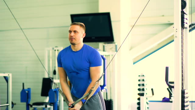 Handsome-sporty-man-is-exercising-in-fitness-club-and-gym-center